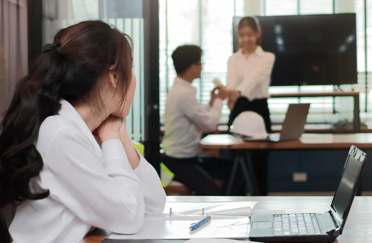 社内で二人で話す男女とそれを見る女性