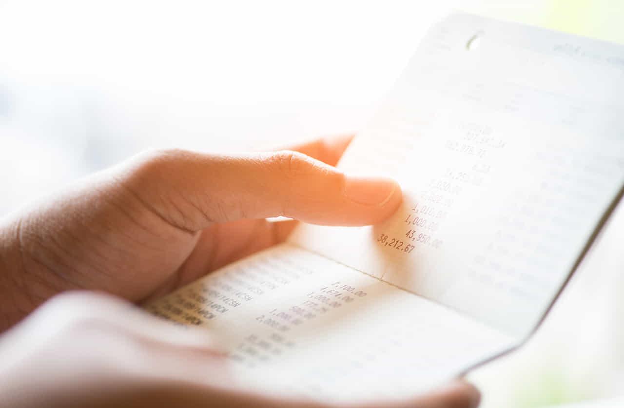 預金通帳を確認する女性の手