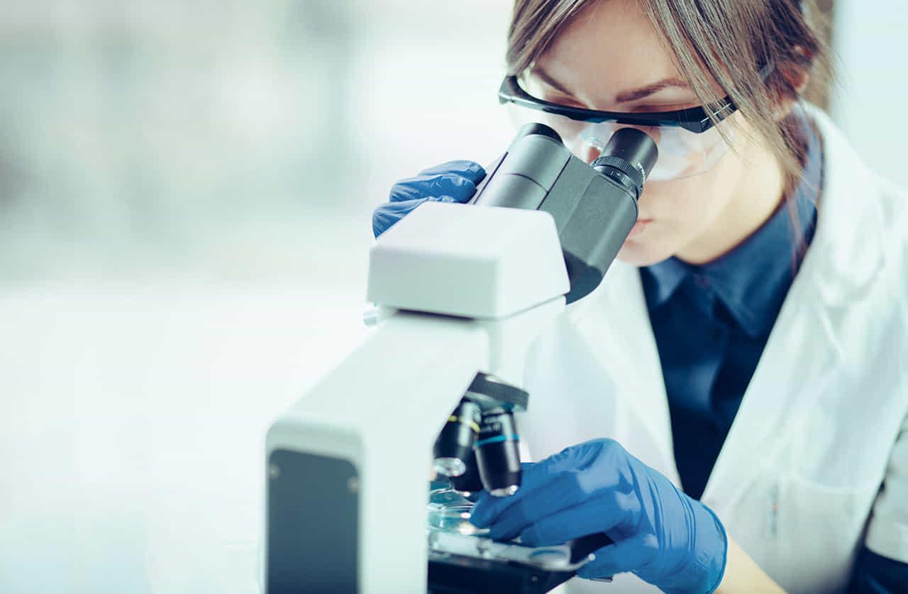 顕微鏡で調べる研究者