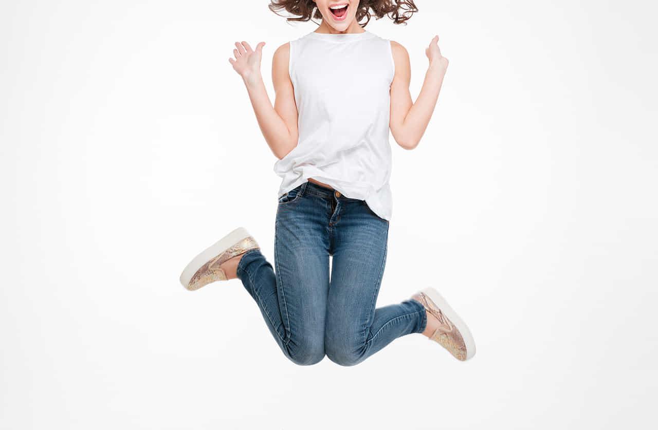 ジーンズに白いのスリーブの女性が嬉しそうにジャンプ
