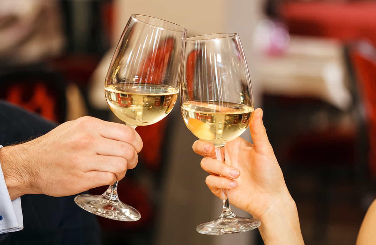 レストランで白ワインで乾杯するカップル
