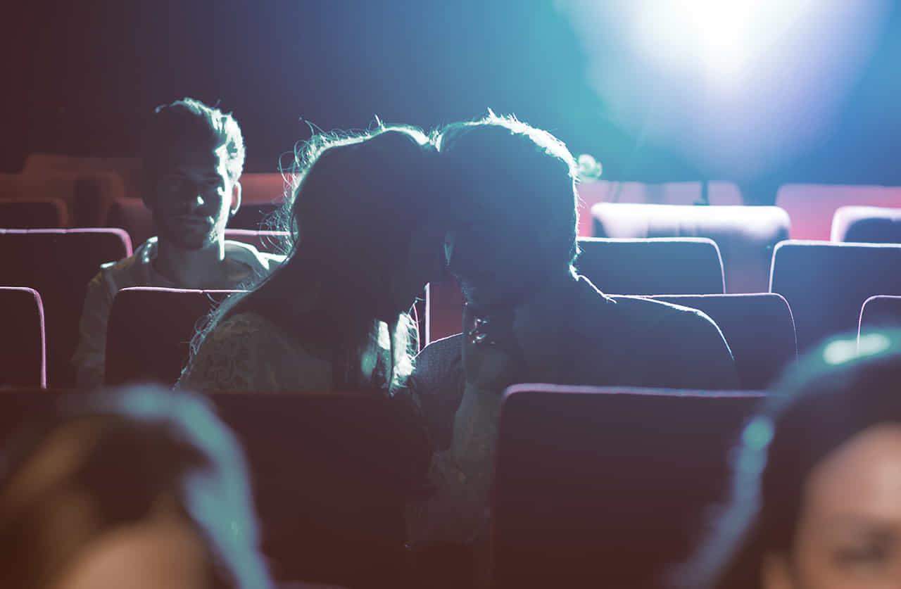 映画館の暗闇の中でキスするカップル