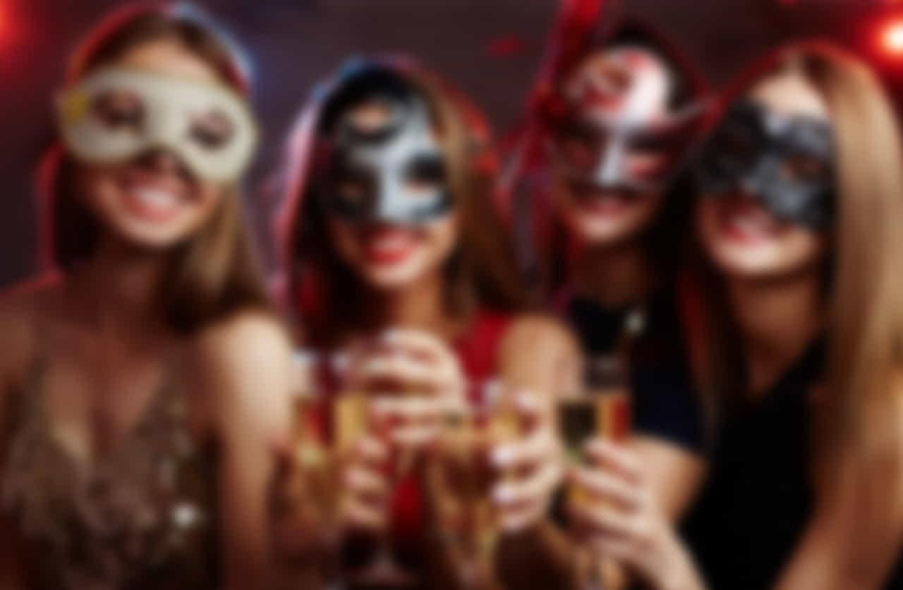 仮面をつけお酒のグラスを持ち微笑む女性たち