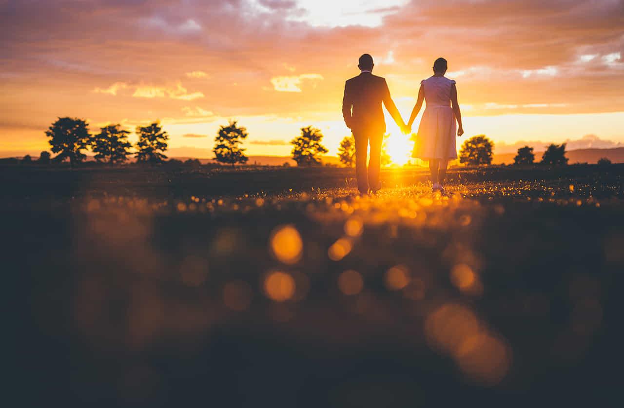 夕陽に向かい二人で手を繋ぎ歩む