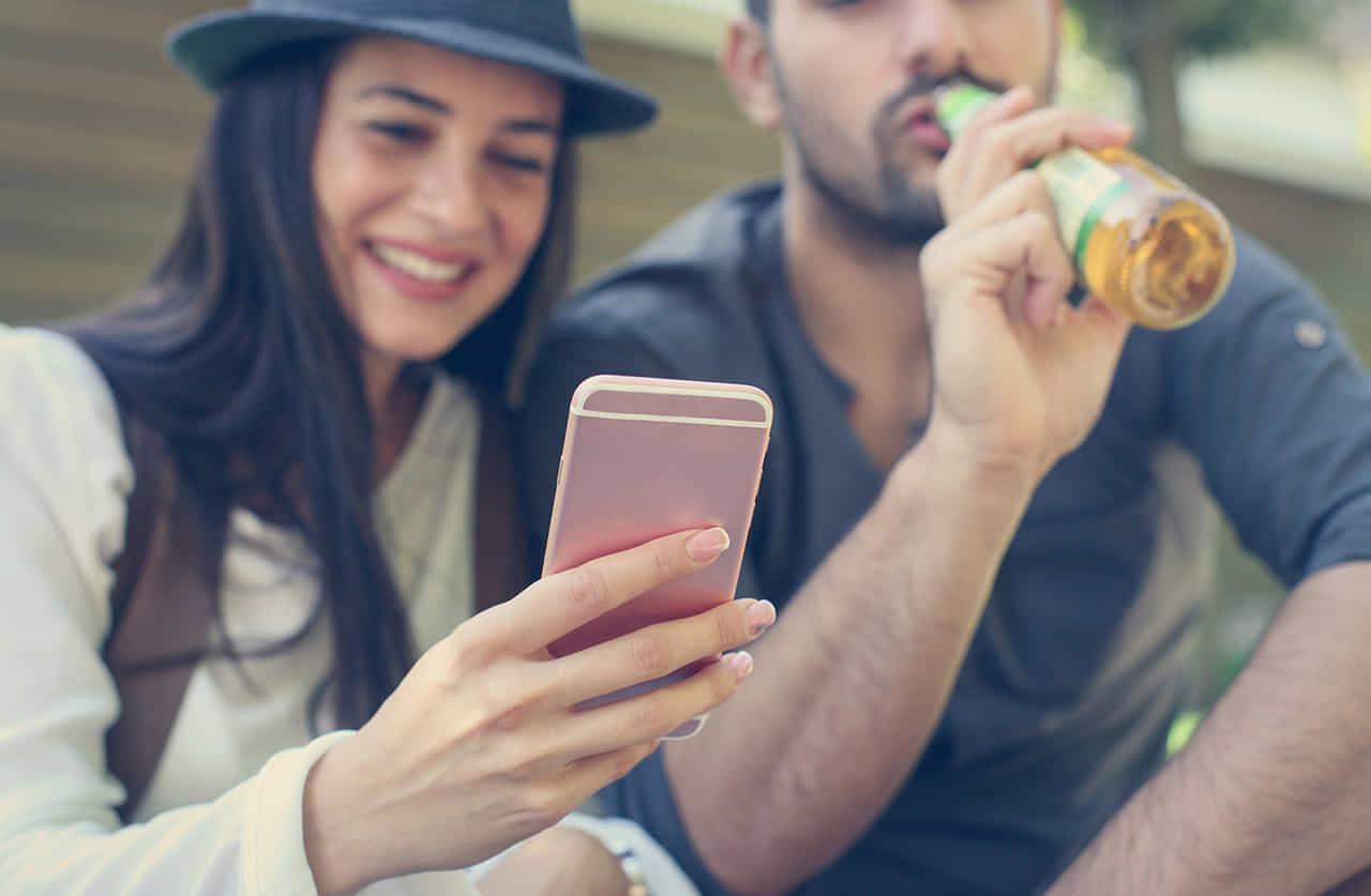 ビールを飲む男性にスマホの画像を嬉しそうに見せる女性