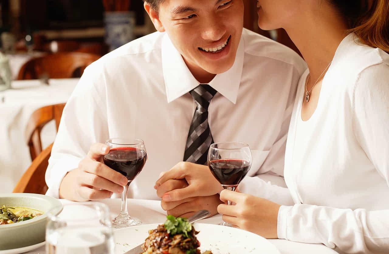 ワインを飲みながら男性の耳元で囁きながら相手の手をさりげなく握る女性