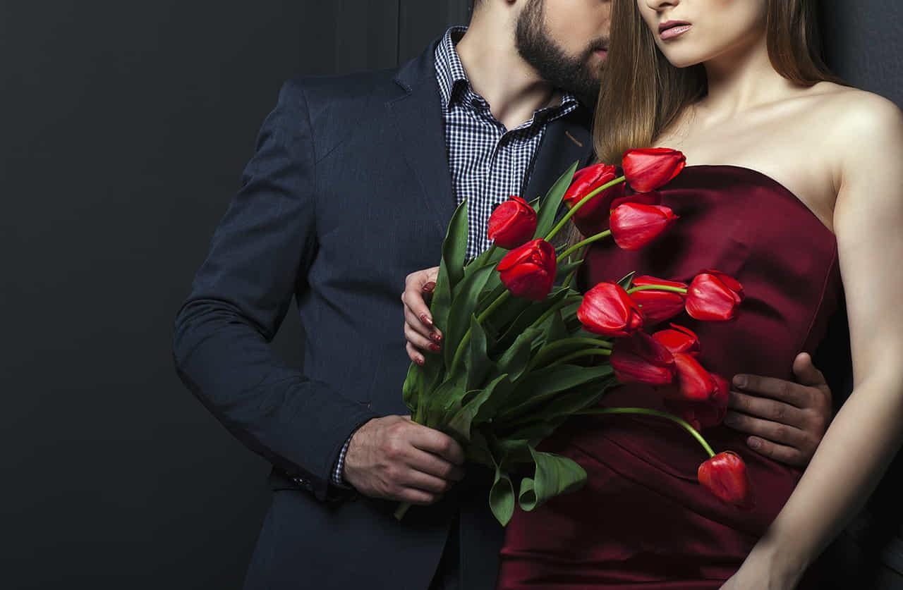 赤いチューリップの花束をドレス姿の女性に贈る男性