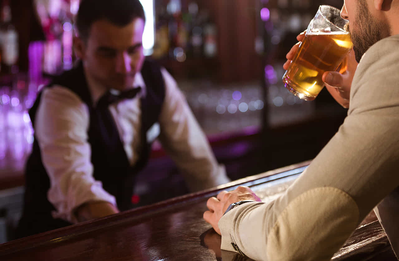 バーのカウンターで一人で飲む男性、目の前にはバーテンダーが仕事をしている