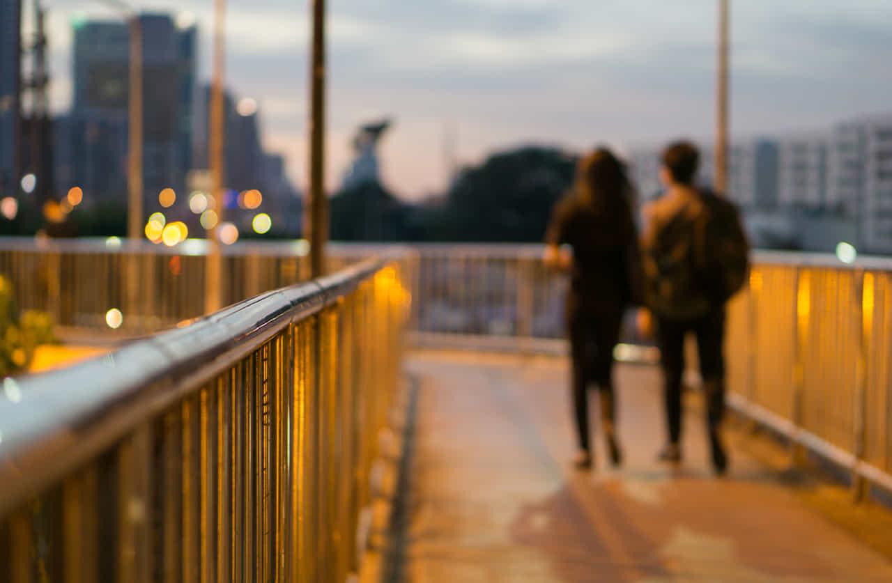 夕暮れの街を歩くひと組のカップルの後ろ姿