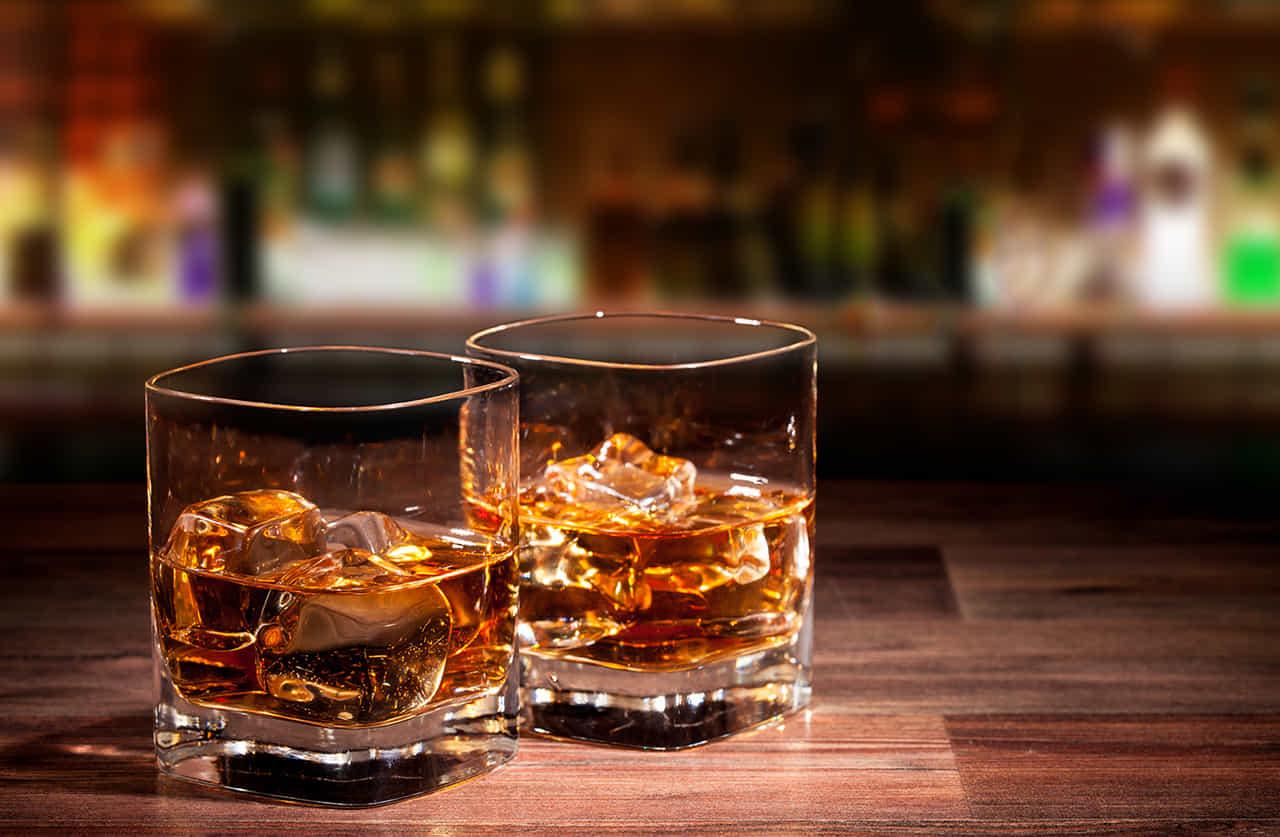 バーカウンターの上にある二つのオンザロックのウイスキー