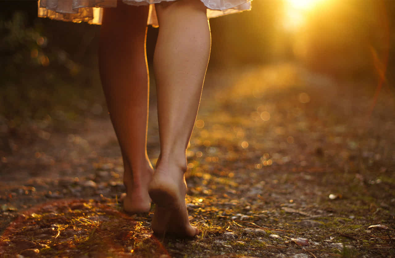裸足で光の指す方へ歩く女性