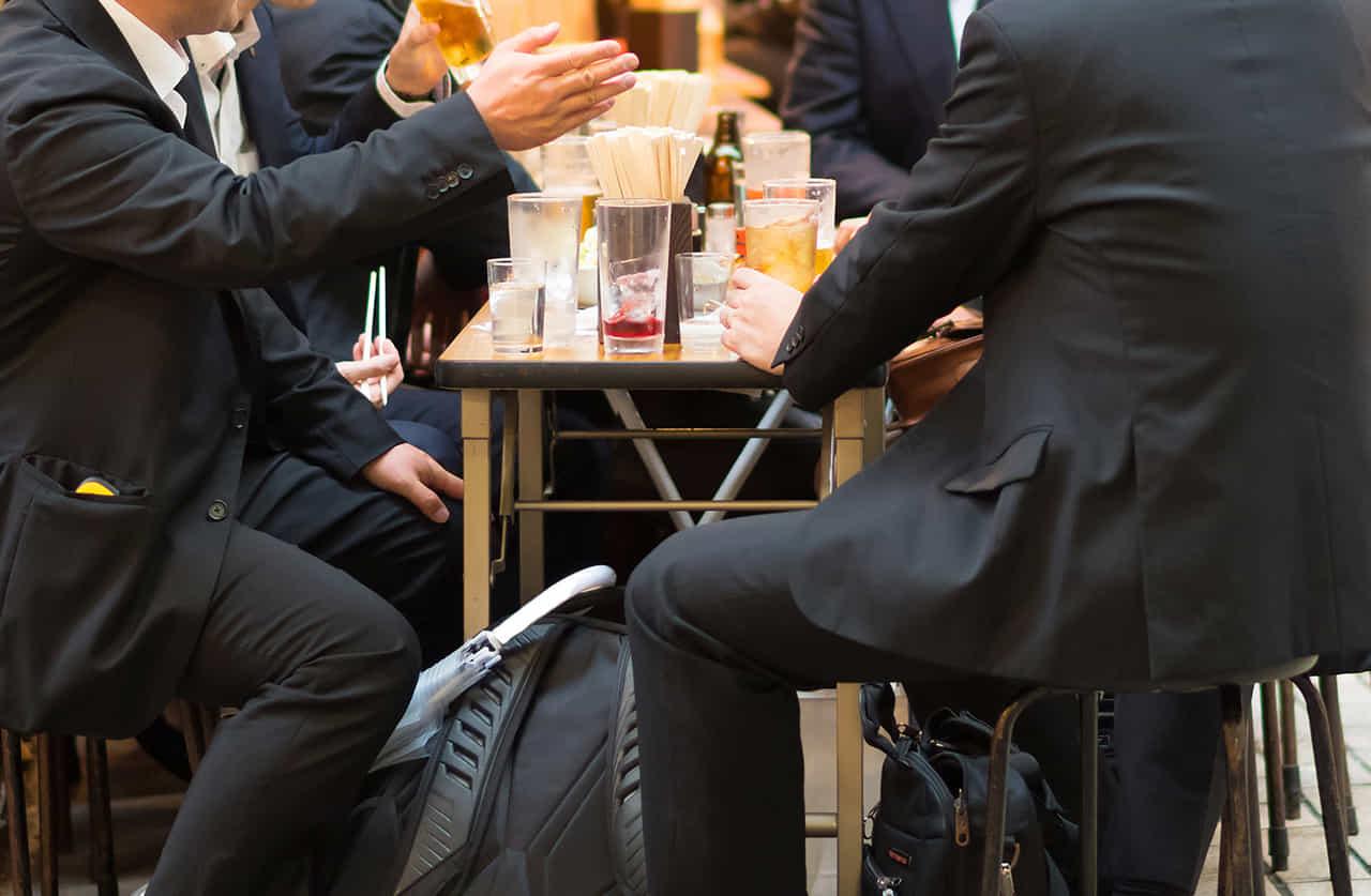 居酒屋でお酒を飲みながら会話を楽しむスーツ姿の男たち