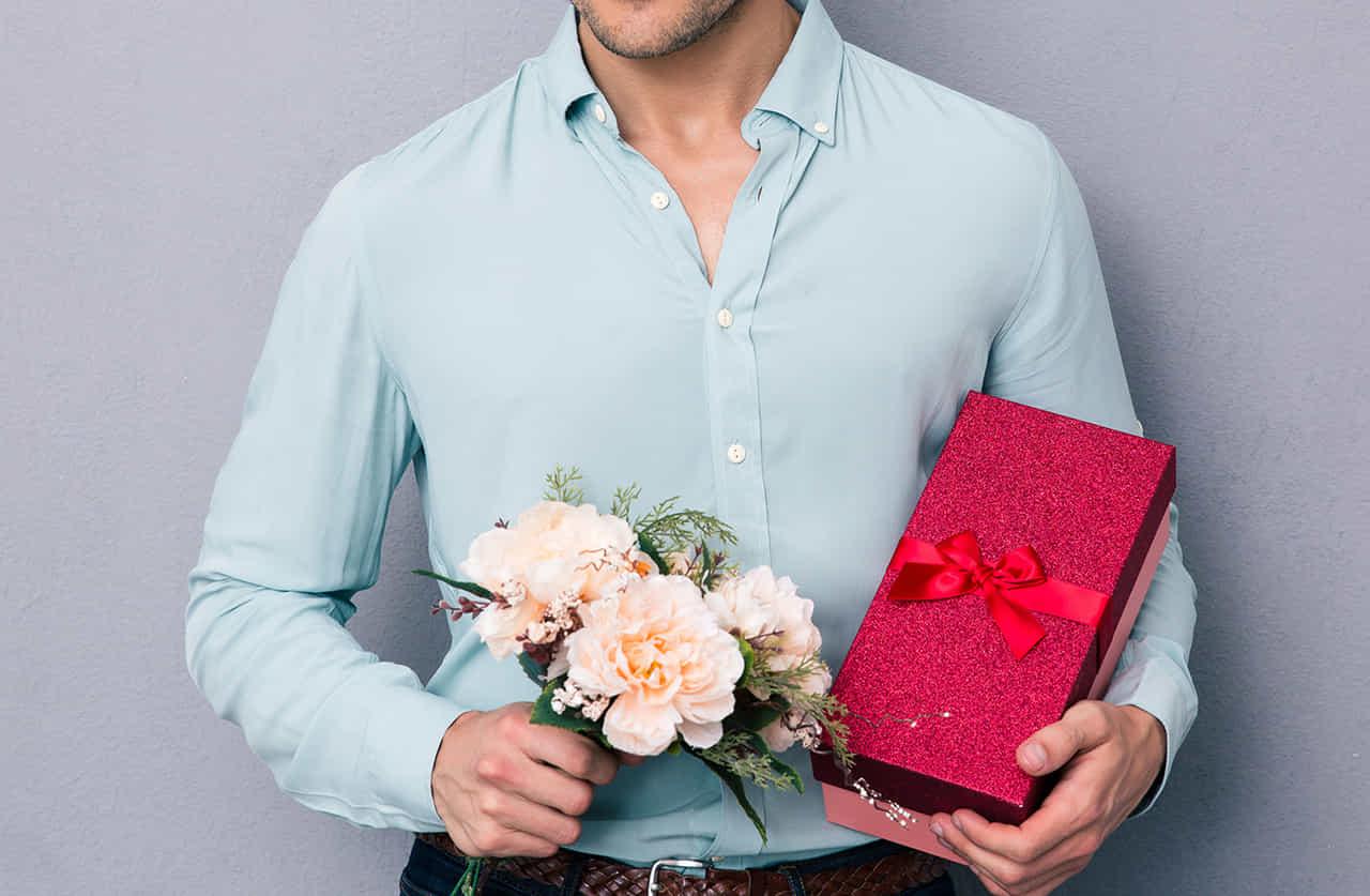 バラの花とプレゼントを持つ男性