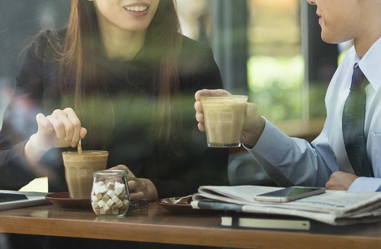 カフェの窓際の席でアイスコーヒーを飲む、主婦とサラリーマンの不倫カップル
