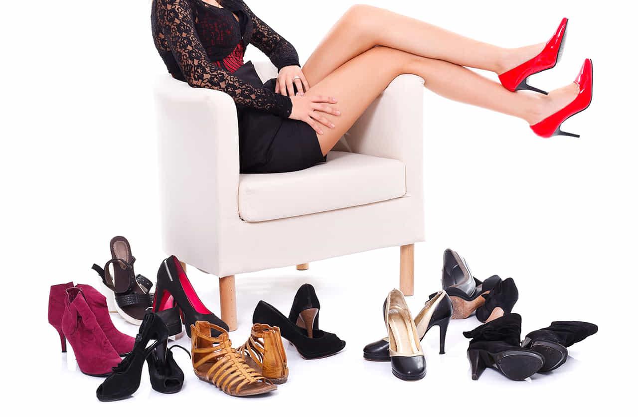 ソファに座り床にたくさんのハイヒールを並べる赤いハイヒールを履いた女性