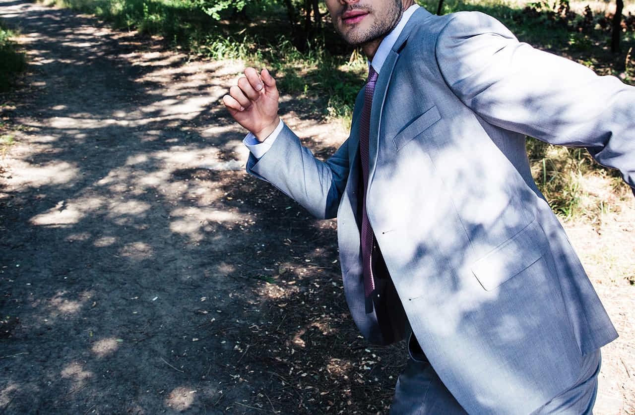 木洩れ陽の舗装されていない道を何かから逃げようとするスーツ姿の男