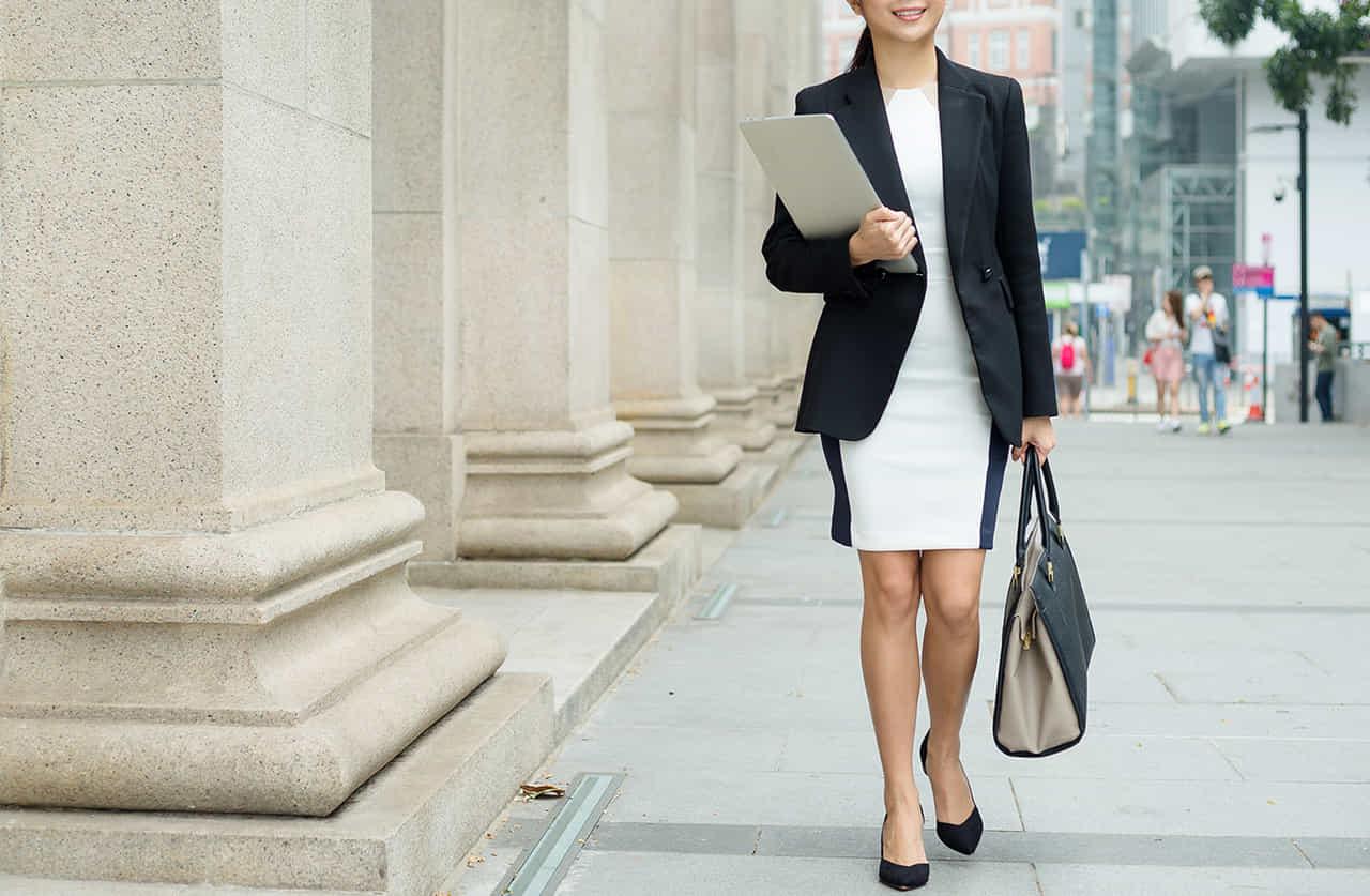 オフィス街を資料を左手に資料をかかえ、右手にバッグを下げるワンピースにジャケットを羽織った女性
