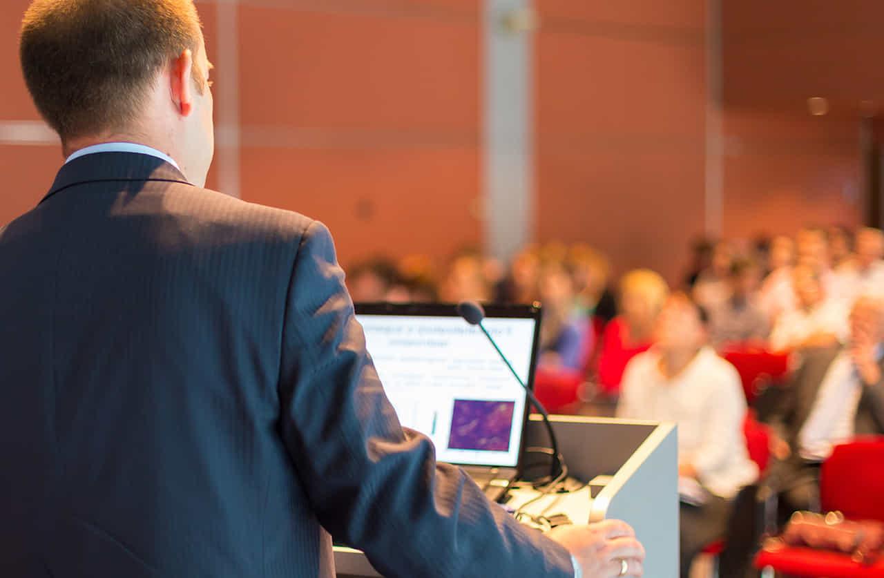 ノートブックパソコンを操り、聴衆の前で公演するスーツの男性の後ろ姿