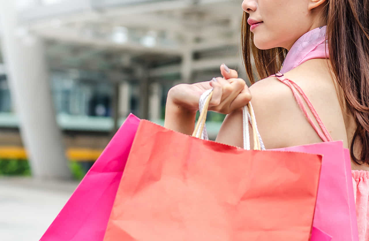 カラフルな男色の紙袋を肩にまわして街をいく女性