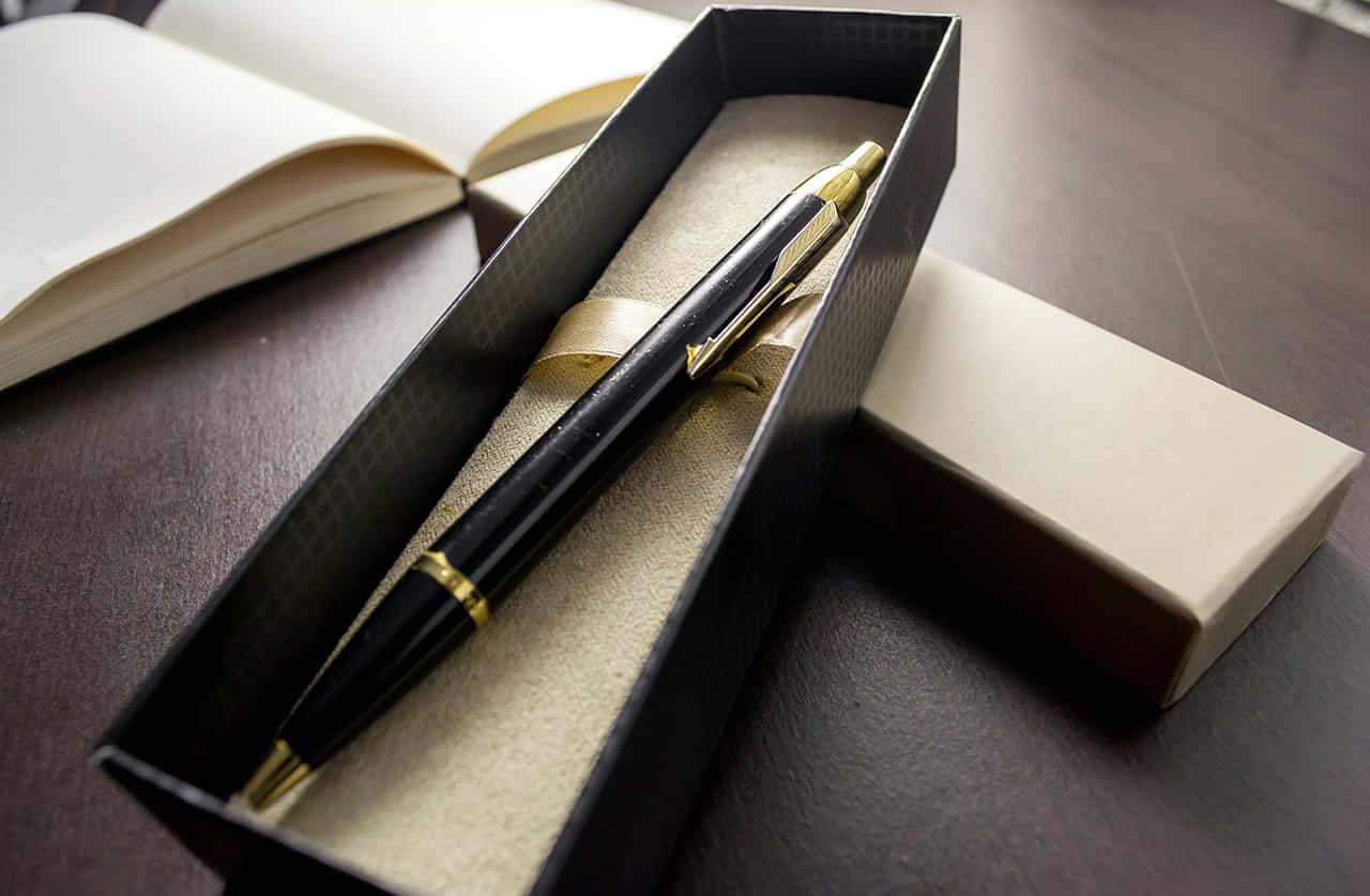 デスクの上で開かれた黒いギフトボックスに入った黒のボディに金のアクセントが入った万年筆