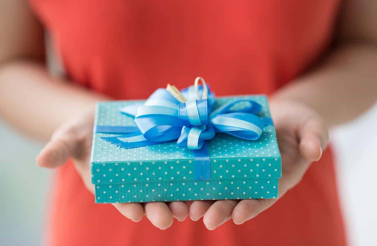 赤いドレス女性が水色の水玉柄の箱にブルーのリボンをつけたプレゼントを差し出している