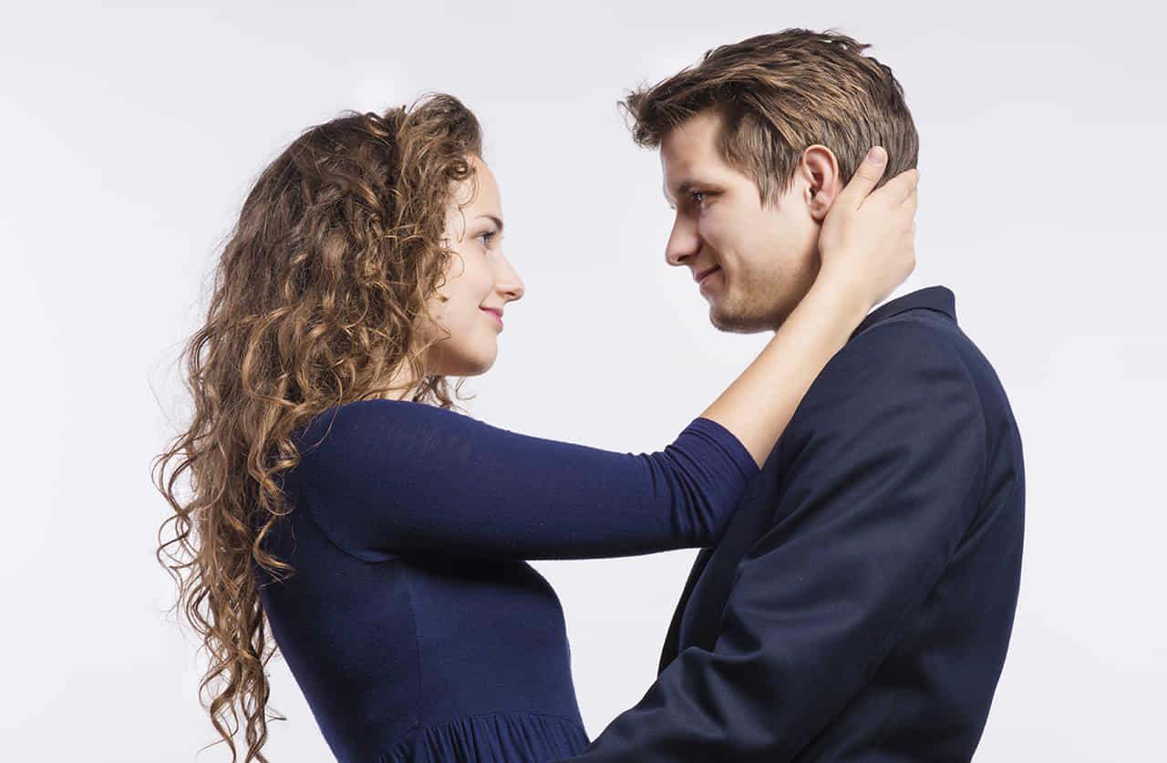 紺野ワンピースを着た女性が、男性の後頭部に右手をまわして見つめ合う
