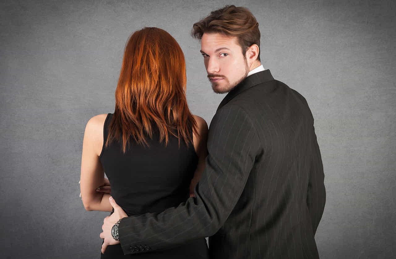 黒のノースリーブの女性の腰に左手をまわし振り返る、グレーのスーツの男性