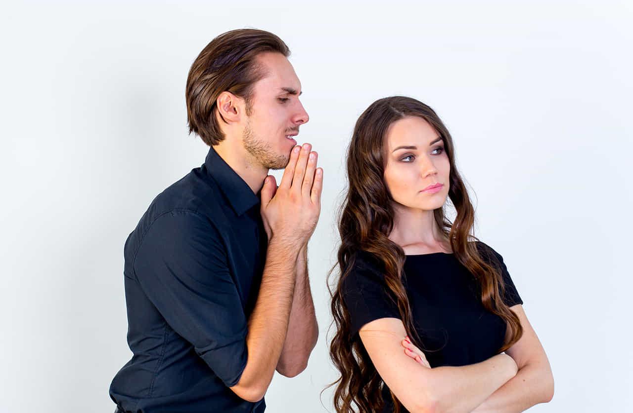 男性が手を合わせて謝るが、それを無視する女性