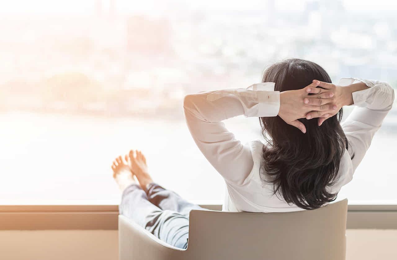 湾岸の風景を望むマンションの窓辺で椅子に座りリラックスする白シャツの女性