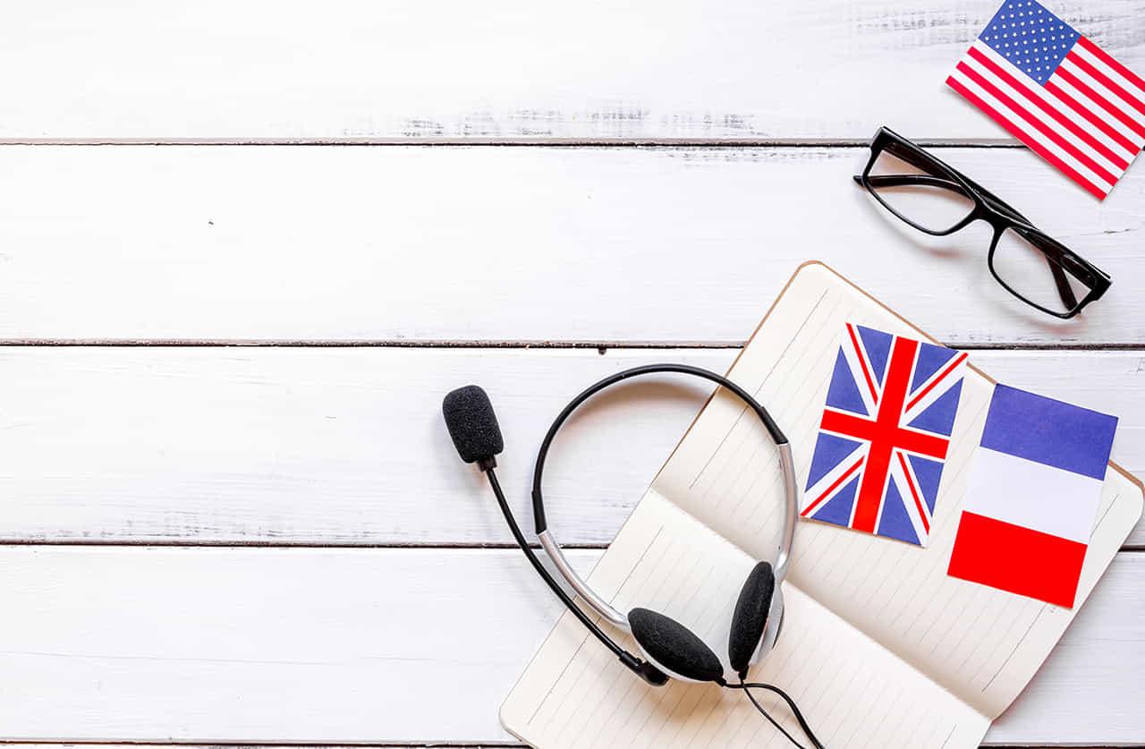 英会話のためのマイク付きヘッドフォンとイギリスとアメリカの国旗とメガネ