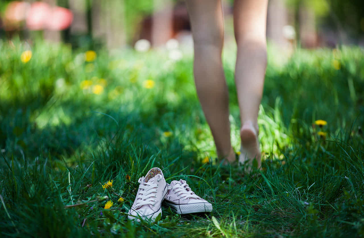 靴を脱ぎ捨て裸足で芝生の上を歩く女性