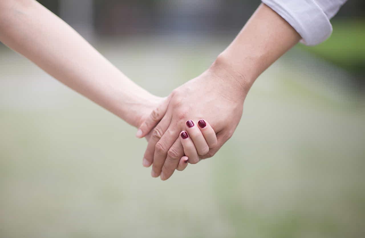 芝生の公園で手を繋ぐ男女