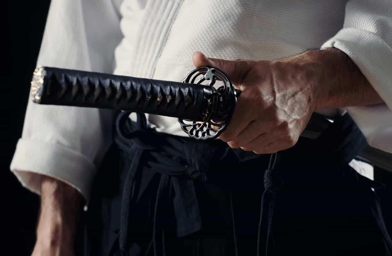 刀の鍔の親指をかける道着を着た武士