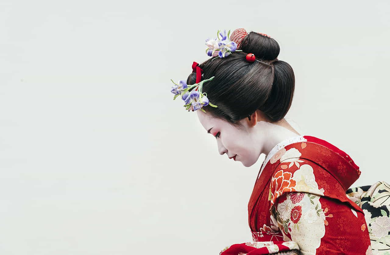 少し顔を伏せている赤い着物を着た芸者の横顔
