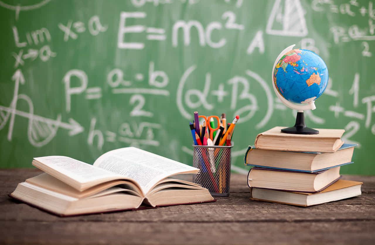 黒板の前に開いた教科書と積み上げた教科書と地球儀とペン立て