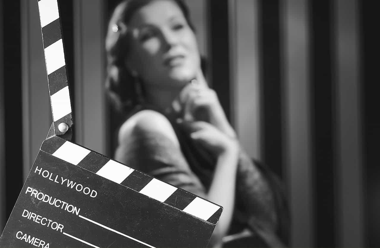 モノクロ映画のイメージ。カチンコの奥で演技をする女優
