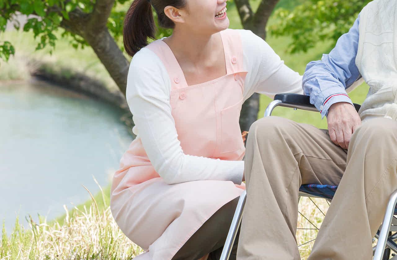 川沿いで車椅子の老人の散歩に寄り添うピンクのエプロンの女性
