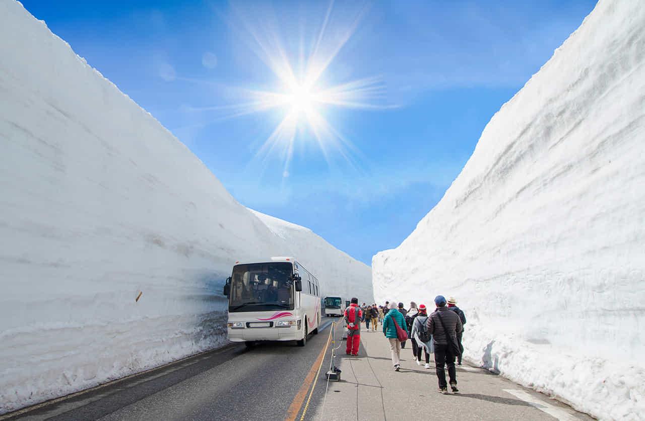 雪の壁に挟まれた立山黒部アルペンルートで観光客を運ぶバス
