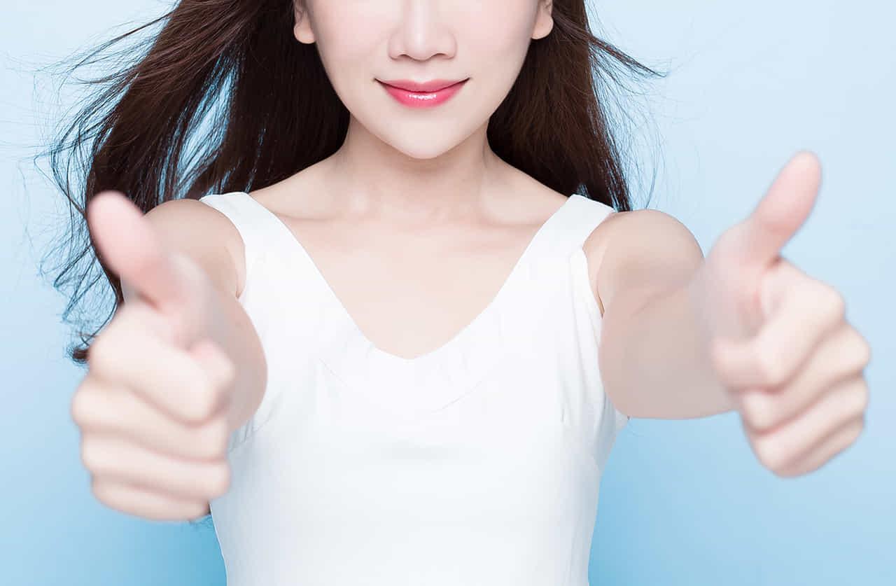 両手を突き出し親指を立てグッドのポーズをする女性