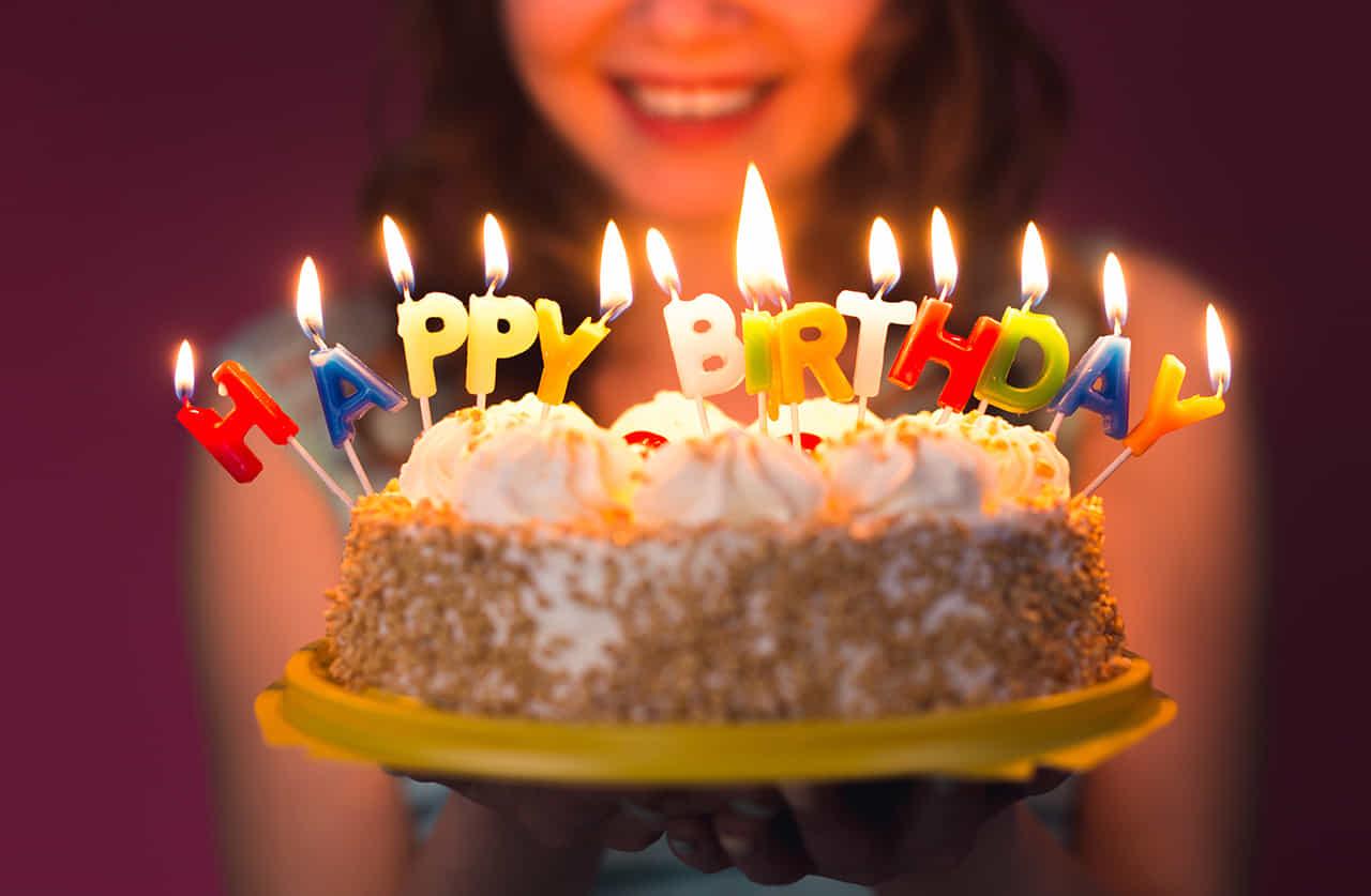HAPPY BIRTHDAYを形どった火のついたロウソクがたったホールケーキを差し出す女性