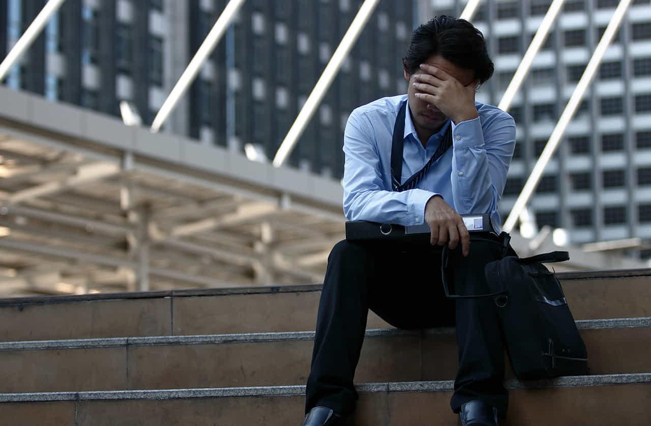 オフィス街の屋外の階段で額に手を当て悩む男性