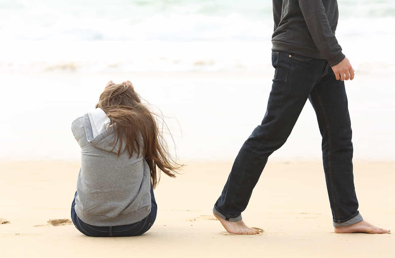 海辺の砂浜に膝を抱えて座る女性から立ち去る裸足の男