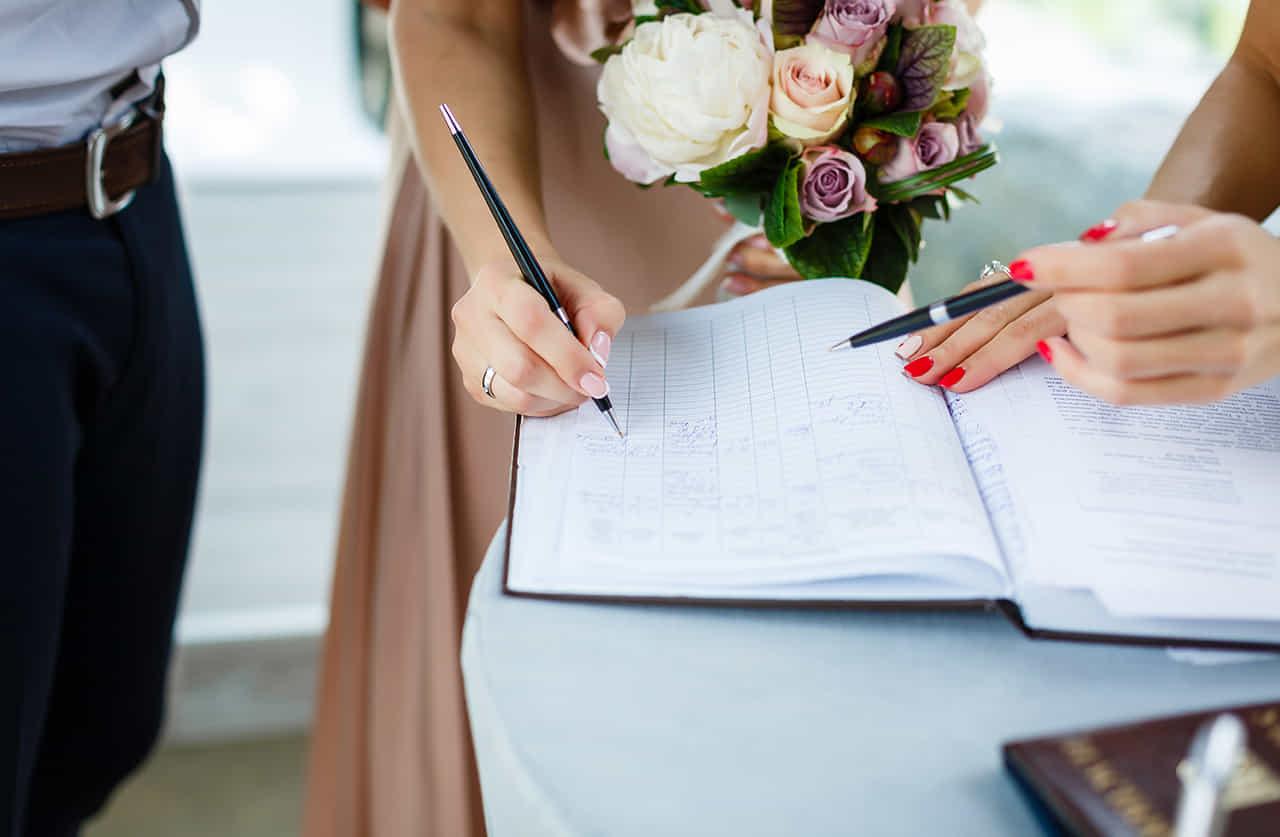 結婚式の受付で記帳をする花束を持った女性