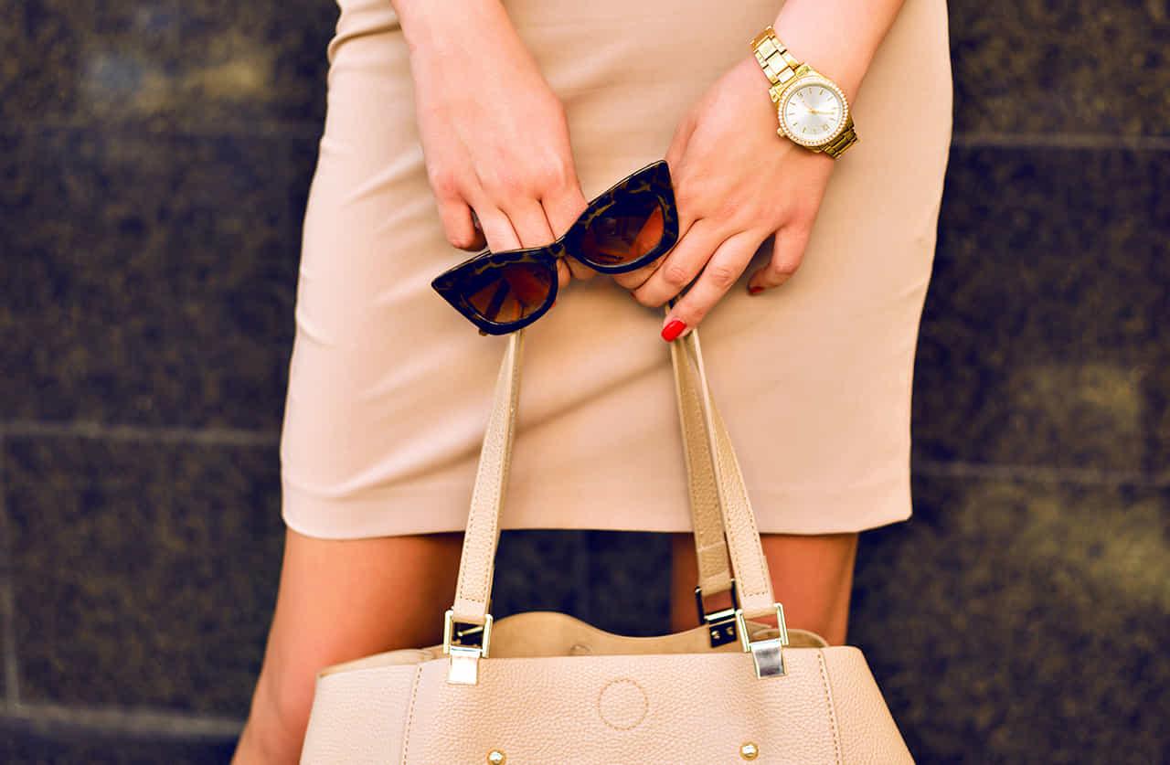 ベージュのワンピースの女性がハンドバッグを下げその手にサングラスを持っている