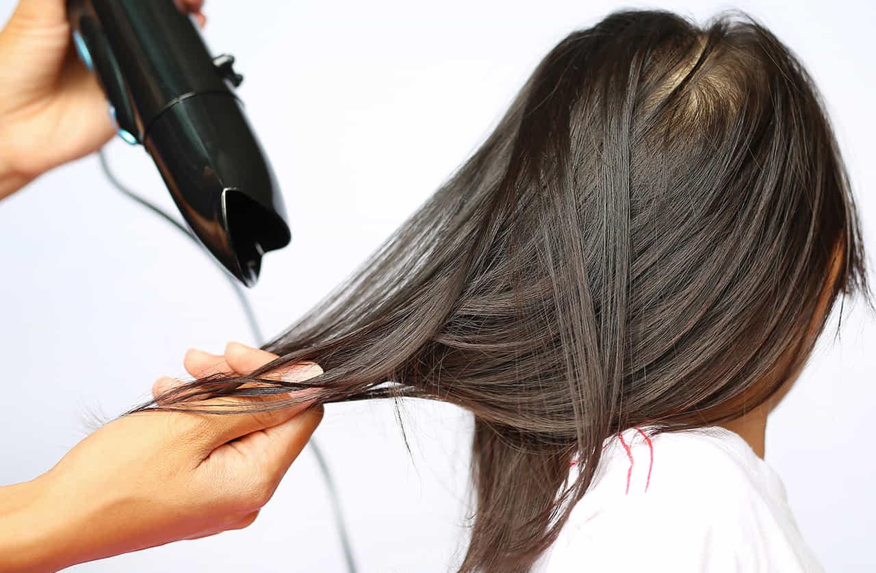 女性の髪をセットするためにドライヤーをあてる美容師の手