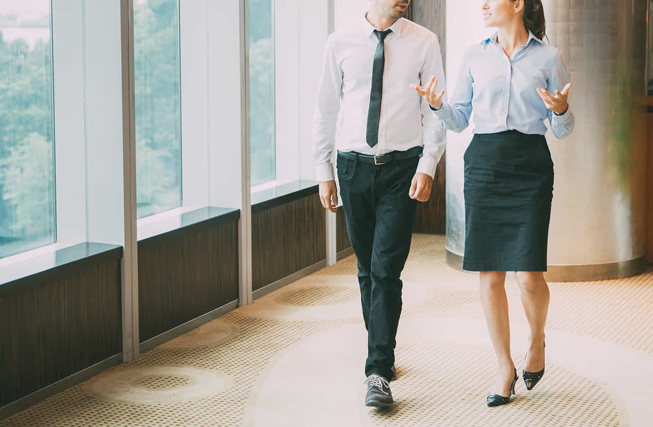 外に面した会社の廊下を仕事の話をしながら歩く男女社員