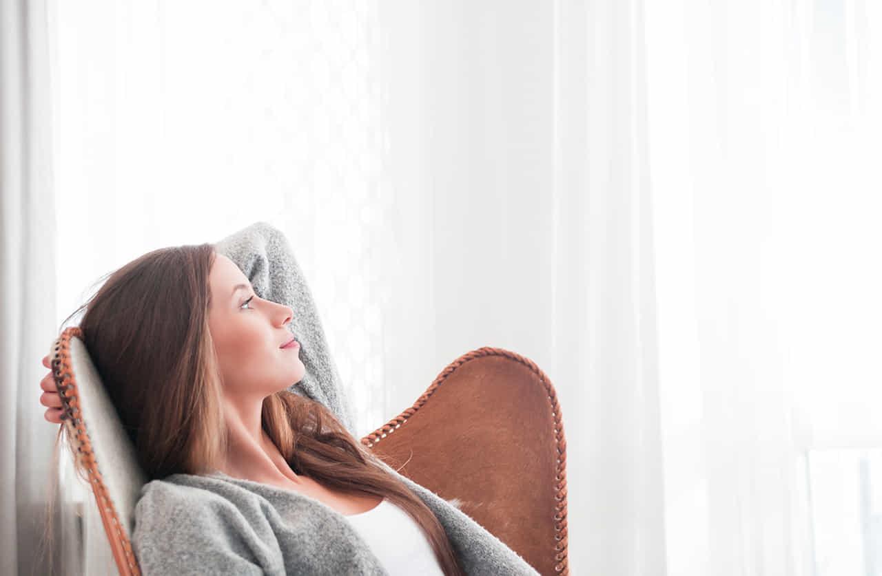 ソファーに体を預け遠くを見つめる女性