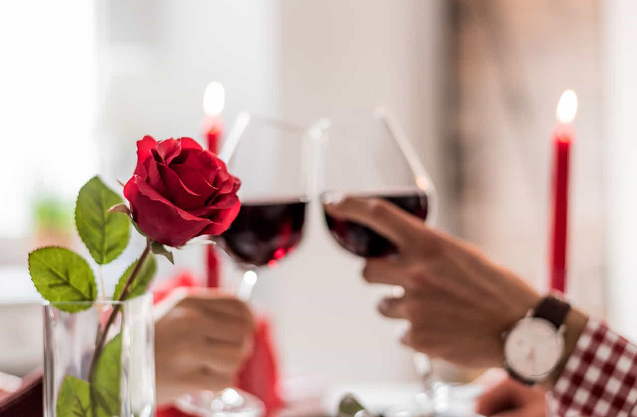 レストランのデーブルに飾られた赤いバラの向こうで赤ワインで乾杯するカップル