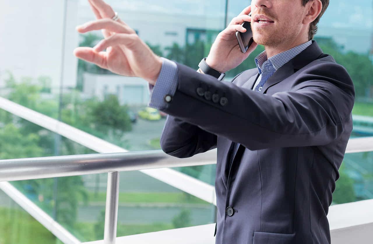 社内の廊下で携帯で話し中に偶然知り合いを見つけジェスチャーで呼び止めようとするスーツの男性