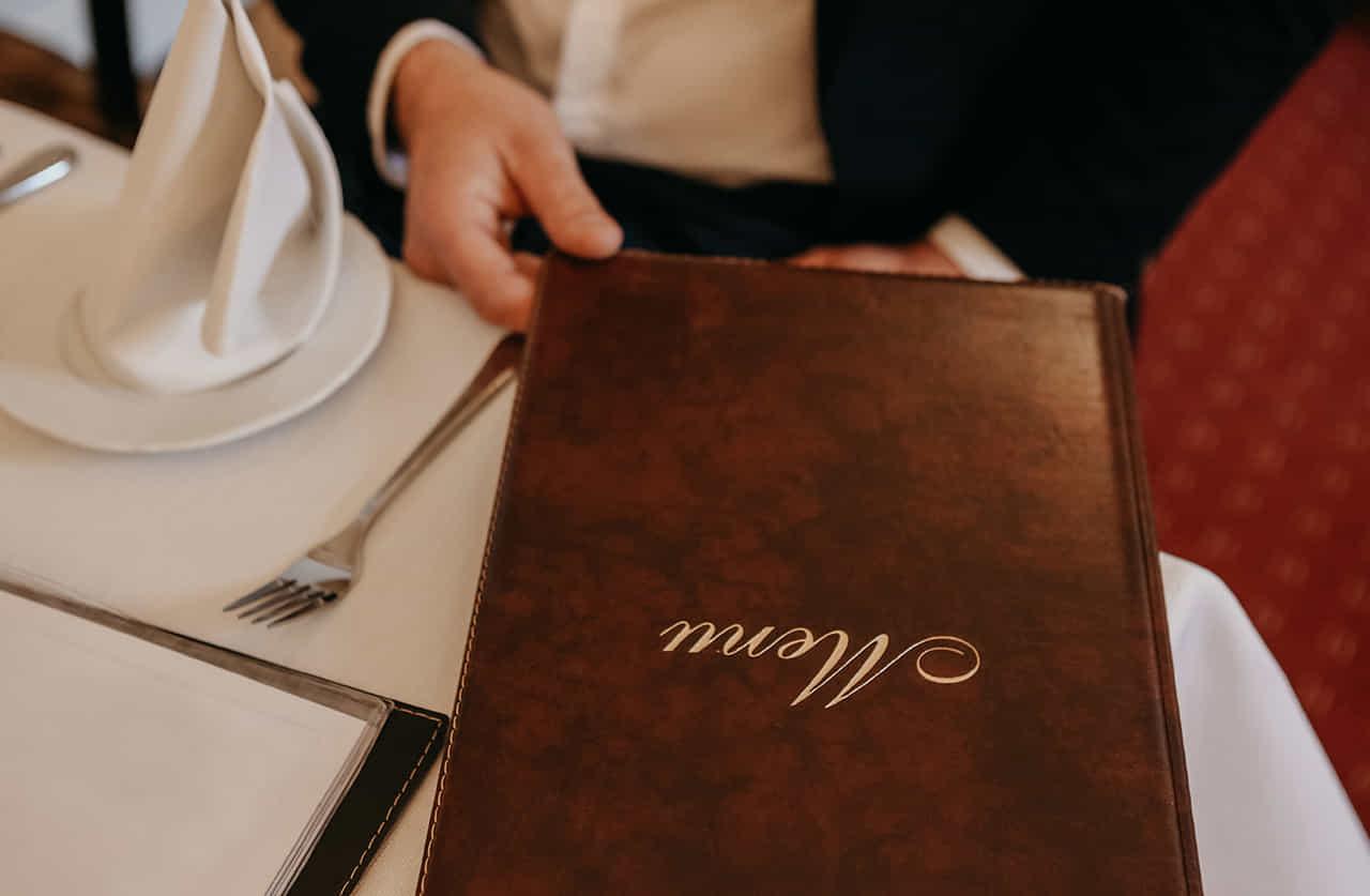 白いテーブルクロスの上に置かれたレストランのメニューを引き寄せるスーツの男